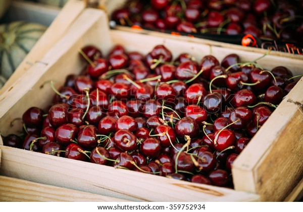 Fresh red ripe sweet cherry berries in wooden box on farmers market