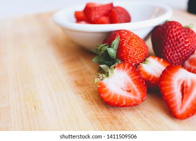 Fresh red strawberries cut in half, placed in a white bowl. And placed on a wooden floor