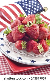 Fresh red strawberries on a stack of patriotic plates with flag background