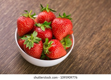 Fresh red strawberry in a bowl on table. Sweet summer dessert background
