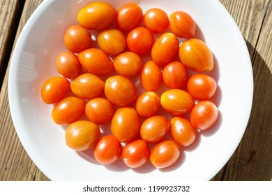 Fresh red tomato from garden in white plate.