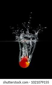fresh red tomato in water splash on black background