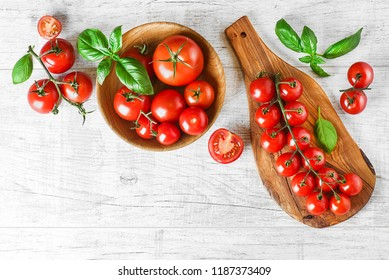 Fresh red variety of tomatoes with basil on white rustic table. Tomato vegetable concept space for text or banner top view.