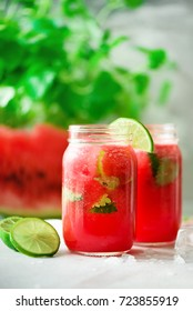 Fresh red watermelon smoothie in glass jar with straw, ice, mint and lime on light background, copy space