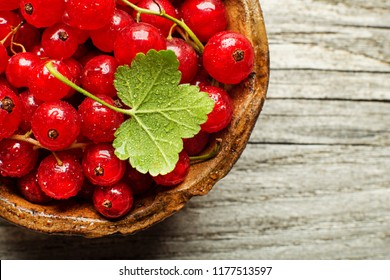 Fresh redcurrant berries on wooden background close up