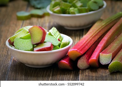Fresh rhubarb in white bowl on wooden table