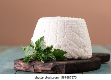 A fresh ricotta cheese with parsley leaf on wooden table, italian food