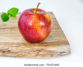Fresh ripe apple on wooden branches with a mint leaf