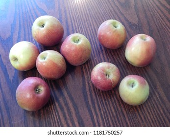 Fresh ripe apples are scattered on a wooden table