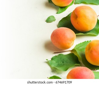A fresh and ripe apricot and branch with green leaves on a white stone background. View from above.