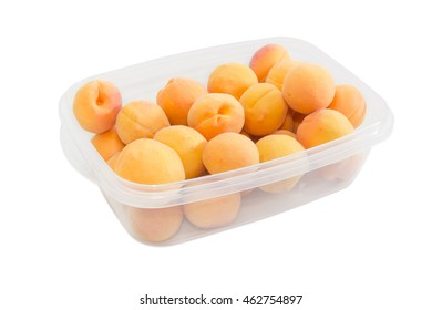 Fresh ripe apricots in plastic tray on a light background closeup