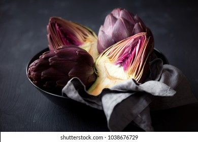 Fresh ripe artichokes in a bowl against black wooden background
