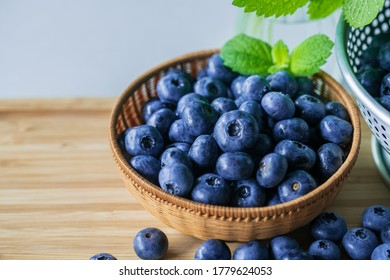 Fresh ripe blueberries in basket on wooden background.