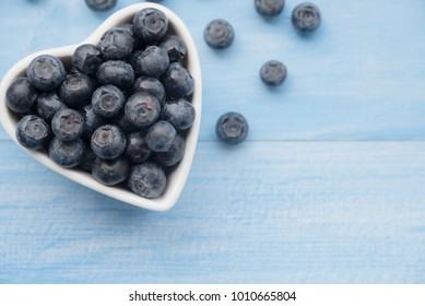 Fresh ripe blueberries fruits in love heart ceramic cup bowl on wooden table. Concept about love and relationship. Healthy fruits clean diet foods, with copy space, top view.