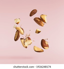 Fresh ripe brazilian nuts falling in the air isolated on pink background. High resolution image. Food levitation concept