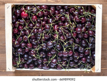 Fresh ripe cherries box on wooden table top view