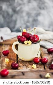 Fresh ripe cherries in a mug on rustic background