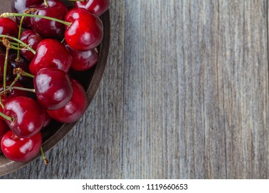 Fresh Ripe Cherries in a rustic wooden bowl