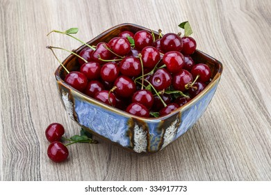 Fresh ripe Cherry in the bowl on wood background