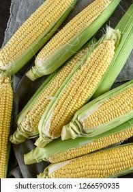 fresh ripe corn cobs on a gray linen napkin, top view