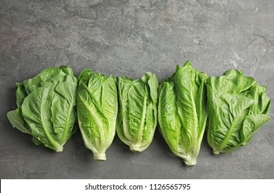 Fresh ripe cos lettuce on gray background, top view