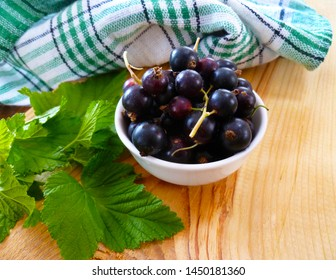 Fresh ripe currants berries. Redcurrant, blackcurrant fruit in white bowl with green leaves on wooden background.  Summer healthy food. Juicy natural fruit. Close up, selective focus, vertical.