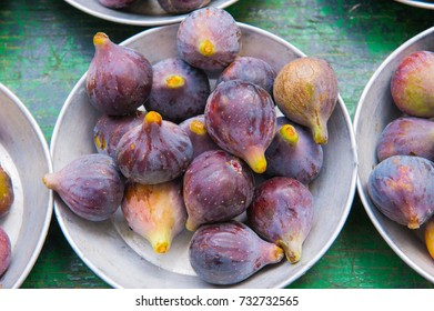 Fresh ripe figs in a bowl closeup on a green background