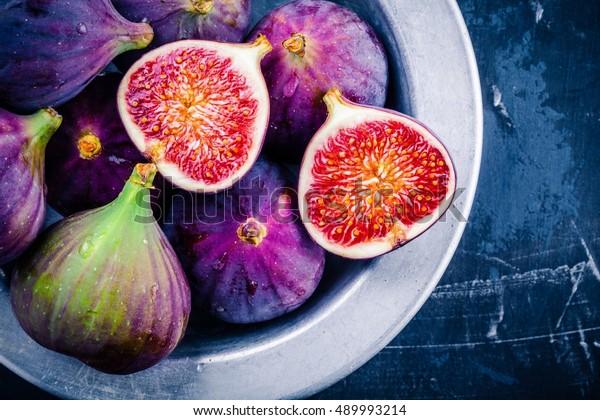Fresh ripe figs in a bowl closeup on a dark background