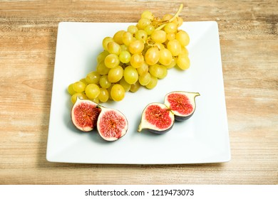 Fresh ripe figs and grapes in a bowl.