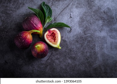 Fresh ripe figs with green leaf and on dark table black background. Healthy Mediterranean fig fruit. Beautiful blue-violet figs with empty copy space close up.