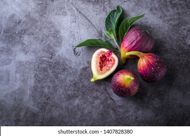 Fresh ripe figs with green leaf and on dark table black background. Healthy Mediterranean fig fruit. Beautiful blue-violet figs with empty copy space close up