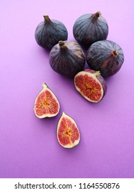 Fresh ripe figs on a purple background. Food photo. Sweet sliced figs on a table. Top view. Copy space.