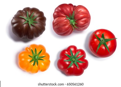 Fresh ripe globe and ribbed heirloom tomatoes with sepals, whole. Top view, clipping paths for each tomato, shadows separated