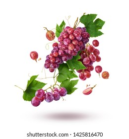 Fresh ripe grapes with leaves falling in the air isolated on white background