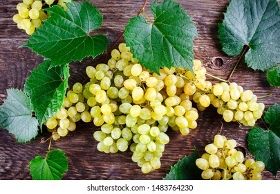 Fresh ripe grapes with leaves on a wooden background, copy space