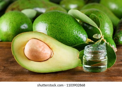 Fresh ripe green avocados and natural avocado oil on wooden table. Healthy eco product of organic farming. Skin, body and hair care. Handmade cosmetic. Home spa.