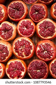 Fresh ripe half cut pomegranates  on  wooden background. Market of Tel Aviv. Israel.