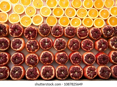 Fresh ripe half cut  pomegranates  and oranges. Market of Tel Aviv. Israel.