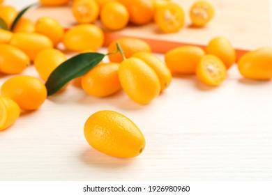 Fresh ripe kumquats on white wooden table, closeup