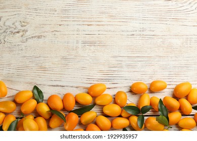 Fresh ripe kumquats on white wooden table, flat lay. Space for text - Shutterstock ID 1929935957