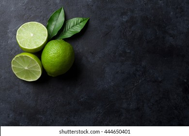 Fresh ripe limes on dark stone background. Top view with copy space