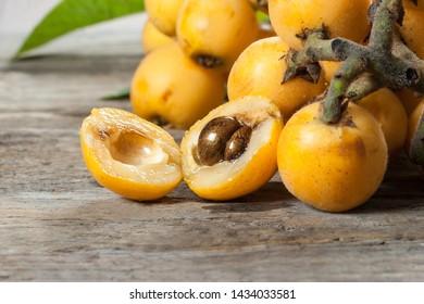 Fresh ripe loquat japanese medlar fruit with branch and leaf on wooden background, malta plum, summer fruits concept
