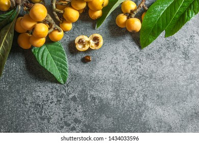 Fresh ripe loquat japanese medlar fruit with branch and leaf on grey rustic table, malta plum, summer fruits concept