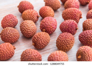 Fresh ripe lychee fruit with peel on wooden table