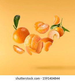 Fresh ripe mandarine with leaves falling in the air. Cut and whole mandarine isolated on yellow background. Food levitation concept. High resolution image