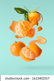 Fresh ripe mandarine with leaves falling in the air. Cut and whole mandarine isolated on turquoise background. Food levitation concept. High resolution image