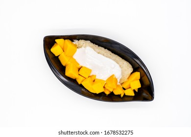 Fresh ripe mango and sticky rice with coconut milk in black bowl on white background, Famous authentic Thai dessert
