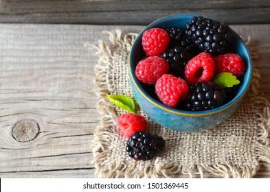 Fresh ripe organic blackberries and raspberries in a blue bowl on rustic wooden table.Summer berries.Healthy eating,vegan food or diet concept. Selective focus.
