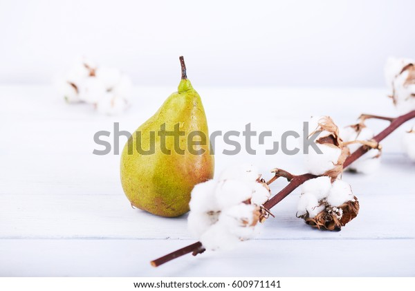 fresh ripe organic pear on white wooden background with cotton flower. High key photo.