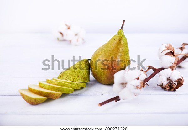 fresh ripe organic pear on white wooden background with cotton flower and another pear cutted into pieces. High key photo.